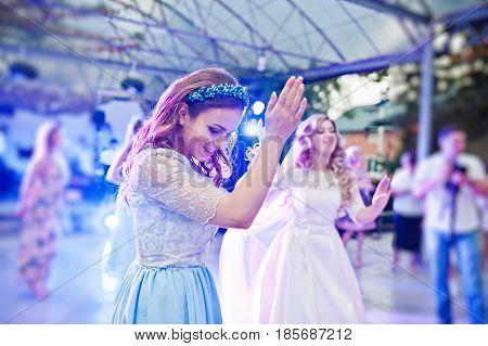 Bridesmaid with bride dancing on wedding party.
