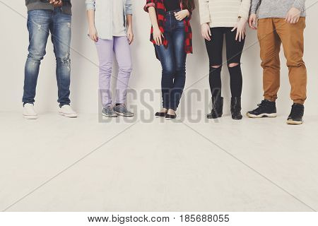 Casual young people, youth fashion. Crop of diverse informal students standing in row indoors on white studio background