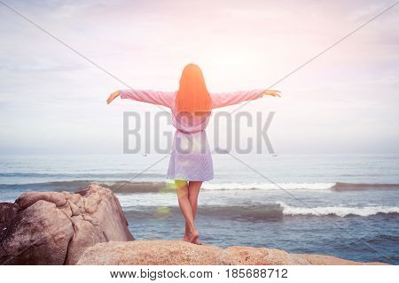 A sunny portrait of beautiful asian woman in blue dress back stand, hands to the sides on a stone by the sea