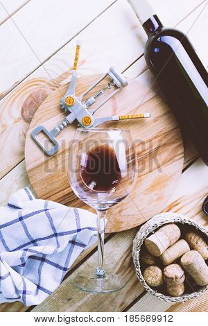 bottle of wine with wine glass on white wooden background