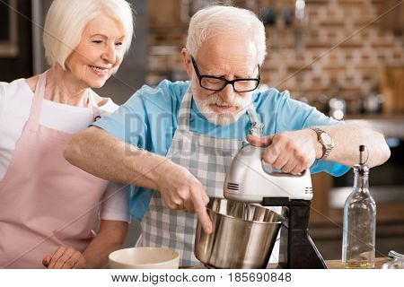 Happy senior husband and wife cooking together and mixing dough