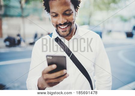 Portrait of Happy African American man in headphone walking at sunny city and enjoying to music on his smartphone.Concept of guy using Internet-enabled electronic device, texting friends.Blurred