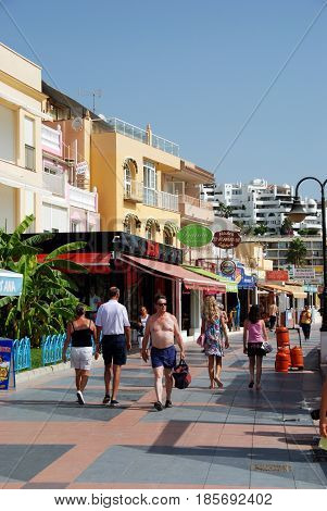 TORREMOLINOS, SPAIN - SEPTEMBER 3, 2008 - Tourists walking along the promenade with shops and restaurants to the left hand side Torremolinos Malaga Province Andalusia Spain Western Europe, September 3, 2008.