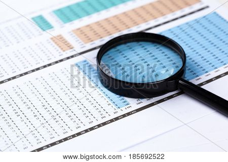 financial documents with magnifying glass over them