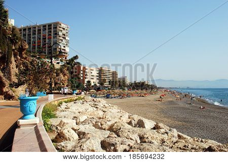 TORREMOLINOS, SPAIN - SEPTEMBER 3, 2008 - Tourists relaxing on the beach and promenade with hotels and apartments to the left Torremolinos Malaga Province Andalusia Spain Western Europe, September 3, 2008.