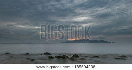 A moody morning slow exposure sky over Nha Trang bay Vietnam just before sunrise.