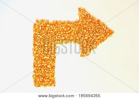 Dry corn kernels are arrows on a white background.