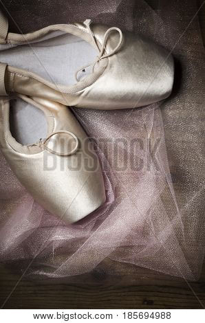 Pointe shoes on wooden background. Ballerina dance shoes with tutu fabric