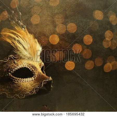 Golden venetian mask over shiny bokeh background with golden texture