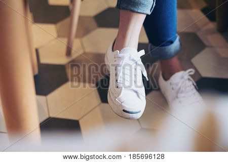 A woman sitting cross legs on a chair with white canvas shoes in modern cafe