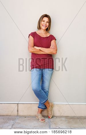 Full Body Happy Older Woman Leaning Against Wall