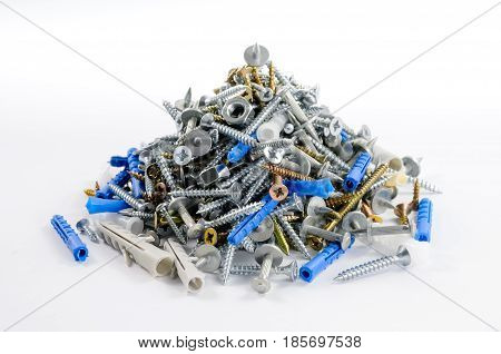 Pile of steel and brass screws and nuts and plastic and metal dowels lying on flat surface