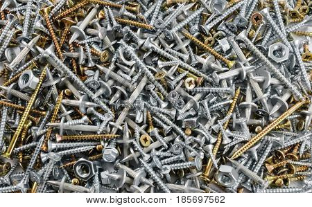 Many steel and brass screws nuts and metal dowels scattered on flat surface