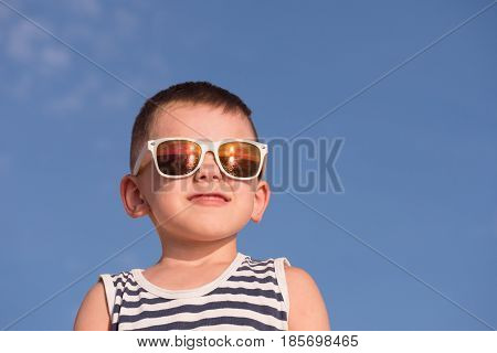 smiling little boy wearing white sunglasses with sea sunset reflection and sailor stripes vest on blue sky background with copyspace