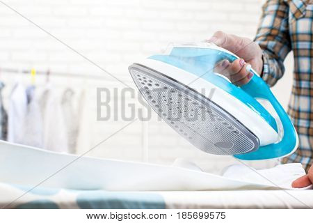 Woman's hands holding hot iron steaming clothes
