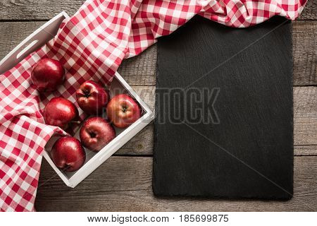 Ripe red apples in birch-box on wooden board with red checkered napkin around and copy space on black slate dish.