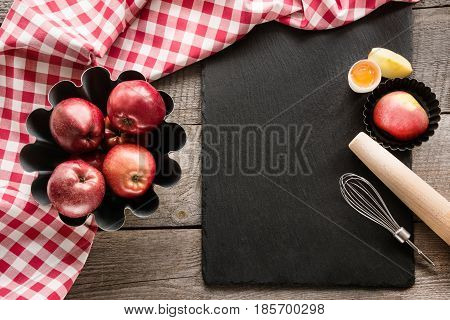 Ripe red apples on wooden board with red checkered napkin around and accessories for baking . Copy space on black slate dish.