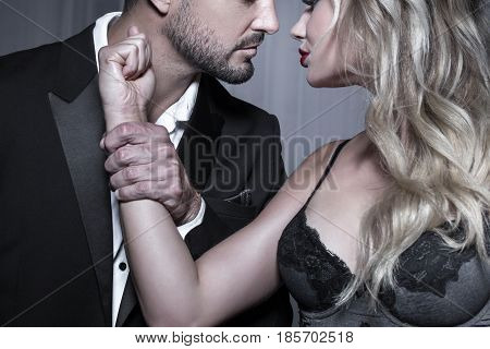 Strong dominant rich man holding blonde lovers hand passionate couple