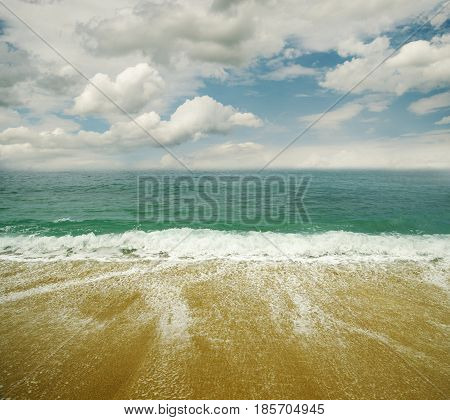 Sandy beach sea and blue sky with clouds.