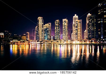 night shot of tall buildings in dubai, near burj khalifa