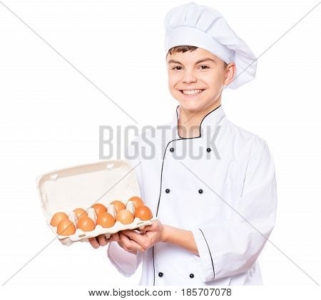 Handsome teen boy wearing chef uniform holding cardboard egg box with ten brown eggs. Portrait of a happy cute male child cook, isolated on white background. Food and cooking concept.