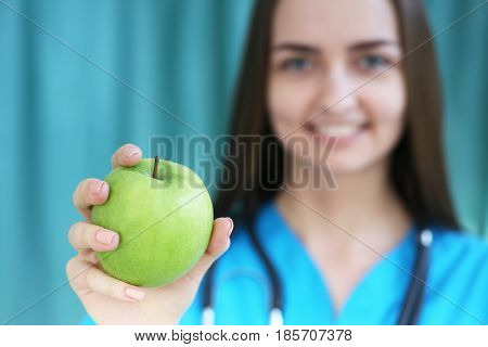 A Female Doctor In A Dietician Holds An Apple In His Hand, Photo With Depth Of Field