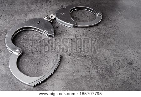 Police handcuff on rough grey background with copy space.
