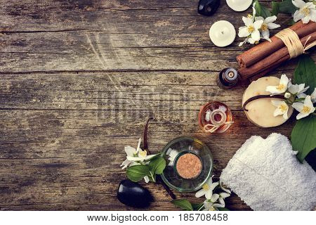 Essential oils with jasmine cinnamon and vanilla on rustic wooden table retor style image.