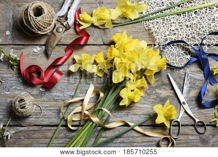 Bouquet of narcissus and gardening tools on rustic wooden table