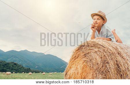 Dreaming boy in straw hat lies on roll haystack
