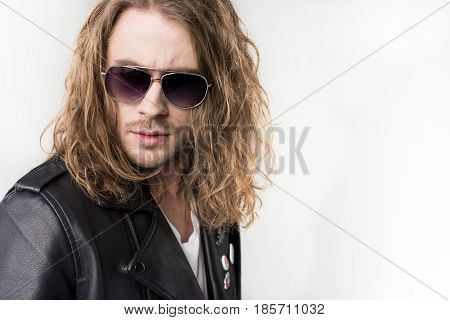 Young Handsome Rocker In Black Leather Jacket And Sunglasses Isolated On Grey