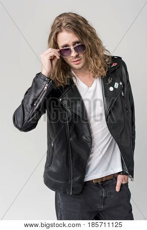 Young Handsome Rocker Posing In Black Leather Jacket And Sunglasses Isolated On Grey