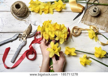 Woman making bouquet of narcissus. top view of hands holding flower arrangement