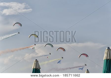 Bellaria Italy - June 05 2016: Five paramotors with colored smoke trails in parade on the beach