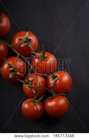 Cherry tomato on rustic black background closeup.
