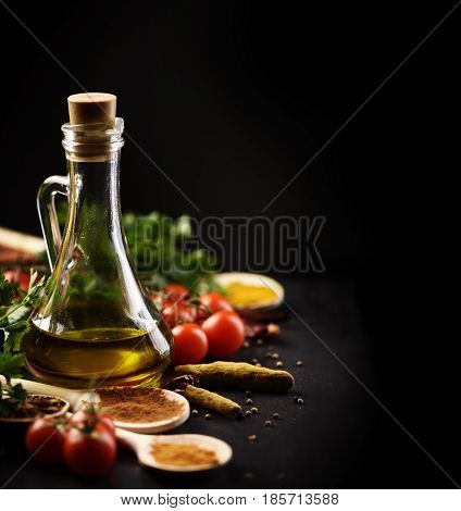 Olive oil and various spices on black rustic background
