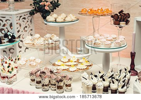 modern stylish luxury wedding candy bar. a wide range of sweets. chocolate, white, orange sweets on gilded paper on the white table. glass stands
