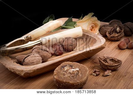 Walnuts, Hazelnuts, Cracked Nuts And Nutcracker In The Wooden Bowl On Brown Wooden Table With Roses.