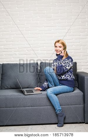 Smiling Woman Holding A Smartphone And Calling While Using Laptop On Sofa
