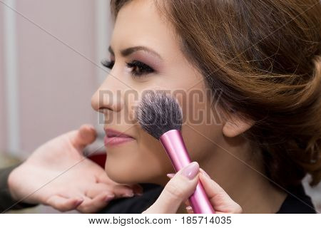 Makeup artist applying makeup to model in salon.