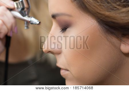 Makeup artist using airbrusher. Makeup artist. Make-up.