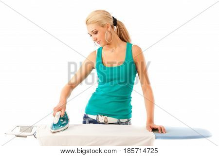 Studio shot of young blond woman ironing