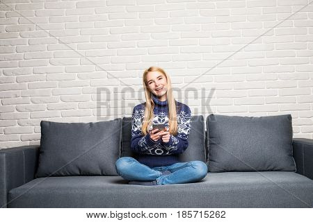 Pretty Young Woman Lying On The Couch And Texting With Her Smartphone