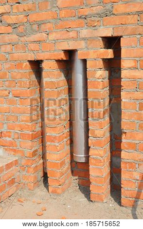 Installed in brick wall metal chimney for fireplace. Stainless steel chimney stove pipe installation.