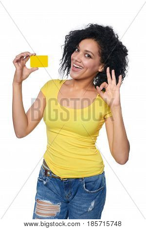 Smiling mixed race african american caucasian woman holding credit card and gesturing OK, isolated on white background