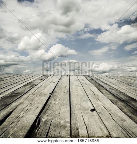 Rustic wooden planks and cloudy sky background design.