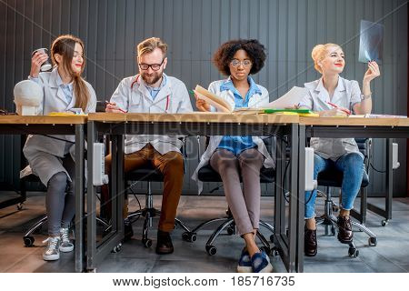 Multi ethnic group of medical students in uniform studying together sitting in a row at the desk in the modern classroom