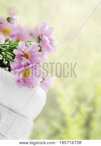 White clean towels and fresh flowers with green natural background