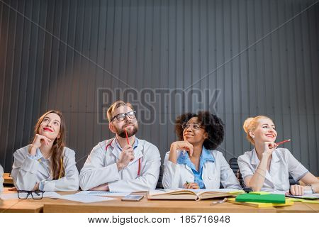Portrait of an thoughtful multi ethnic group of medical students in uniform sitting in a row together at the desk in the modern classroom