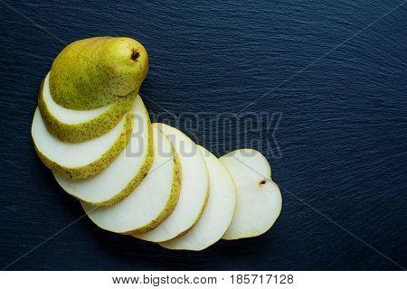 Ripe Pear on the dark slate background.